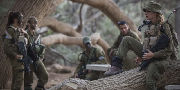 """Soldiers of the Caracal Battalion seen resting before beginning a 16 Kilometer journey overnight to complete their training course, in Azoz village, southern Israel, near the border with Egypt, September 3, 2014. Formed in 2004, the Caracal Battalion is an infantry combat battalion of the Israel Defense Forces, composed of both male and female soldiers, which is stationed along the Egyptian border. Most of the Caracal soldiers are female. Photo by Hadas Parush/Flash90 *** Local Caption *** ???? ???? ???? ??? ????? ????? ???? ????? ?????? ?????? ???? ????? ??? ????? ??""""? ????? ??????"""